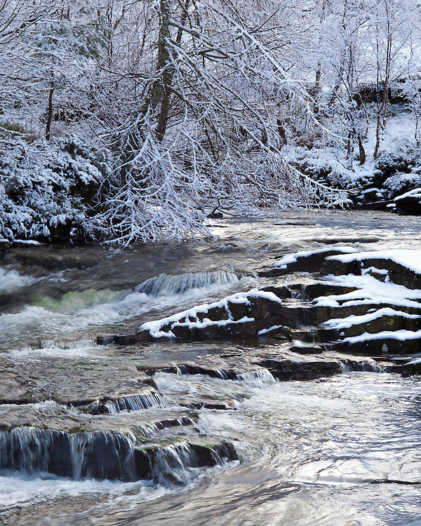 The River Broom makes its way through a snow-covered landscape upstream from Corrieshalloch Gorgeon on its way to the sea at Loch Broom and Ullapool in Scotland.