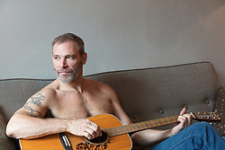 sexy shirtless man in jeans playing the guitar at home