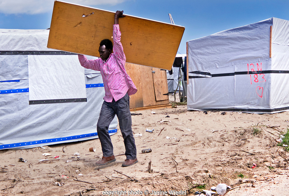 Man carrying board to repair his makeshift home in The Calais Jungle Refugee and Migrant Camp in France