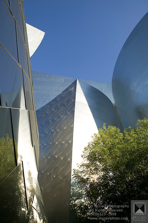 Light and images reflect off the clean metal surface of the Walt Disney Concert Hall with blue sky above and green tree below, 135 North Grand Ave, Los Angeles, CA 90012, Part of Music Center, Performing Arts Center of Los Angeles County, California...Subject photograph(s) are copyright Edward McCain. All rights are reserved except those specifically granted by Edward McCain in writing prior to publication...McCain Photography.211 S 4th Avenue.Tucson, AZ 85701-2103.(520) 623-1998.mobile: (520) 990-0999.fax: (520) 623-1190.http://www.mccainphoto.com.edward@mccainphoto.com.