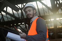 Portrait of a young male engineer holding blueprint and using digital tablet at construction site, Freiburg Im Breisgau, Baden-Wuerttemberg, Germany