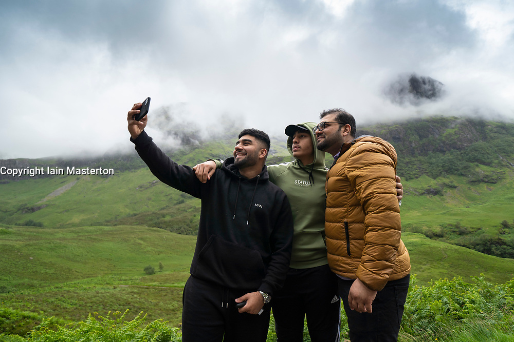 Glen Coe, Scotland, UK. 4 July, 2020. Tourists travel to Glen Coe on first weekend after 5 mile travel restriction was lifted by the Scottish Government. Pictured; cIndian day-trippers take selfie photograph with spectacular mountain backdrop in Glen Coe.  Iain Masterton/Alamy Live News