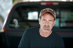 Man with facial hair sitting on the back of a truck