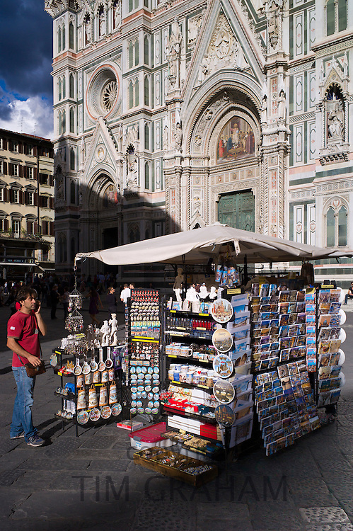 Man using cellphone by souvenir stall selling guidebooks, maps and souvenirs in Piazza di San Giovanni, Tuscany, Italy
