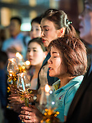 12 AUGUST 2015 - BANGKOK, THAILAND: Thais sing the Queen's Anthem during a candle light program at a shopping mall in Bangkok to honor Queen Sirikit of Thailand on her 83rd birthday. Queen Sirikit was born Mom Rajawongse Sirikit Kitiyakara on August 12, 1932. She is the queen consort of Bhumibol Adulyadej, King (Rama IX) of Thailand. She met Bhumibol in Paris, where her father was the Thai ambassador. They married in 1950, she was appointed Queen Regent in 1956. The King and Queen had one son and three daughters. She has not made any public appearances since her hospitalization in 2012. Her birthday is celebrated as Mother's Day in Thailand, schools and temples across Thailand hold ceremonies to honor the Queen and mothers.    PHOTO BY JACK KURTZ