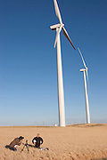265-foot wind turbines tower over wheat fields in Birds Landing, California as Peter Menzel photographs John Opris with his day's worth of food for a book. (From the book What I Eat: Around the World in 80 Diets.) Each 265-foot wind turbine produces enough electricity per year to power 350 average-size California homes. MODEL RELEASED.