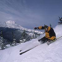 Keith Rollins skis powder at Crystal Mountain, WA, Mount Rainer bkg.