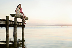 Mature couple sitting on pier looking over lake, Bavaria, Germany