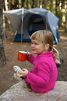 A 5 year-old girl having a drink at her campsite.