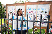 Pam Bosley poses in front of the memorial wall outside the The Ark of St. Sabina with a poster demanding justice for her son Terrell Bosley who was shot and killed in 2006.