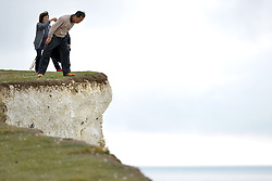 © Licenced to London News Pictures. 14th October 2017. Birling Gap, East Sussex. Tourists visiting the iconic Seven Sisters chalk cliffs near Birling Gap, East Sussex, get dangerousy close to the crumbling edge just days after an inquest conculded that South Korean tourist, Hyewon Kim, 23, died after falling from the cliffs whilst posing for a selfie. Photo credit: Peter Cripps/LNP