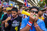 """14 JANUARY 2014 - BANGKOK, THAILAND:  Anti-government protestors blow horns and whistles in front of Royal Thai Police headquarters. The whistle has emerged as the protestors' main weapon against the government. Hundreds of protestors picketed police headquarters because they accuse the police of siding with the government during the protests. Tens of thousands of Thai anti-government protestors continued to block the streets of Bangkok Tuesday to shut down the Thai capitol. The protest, """"Shutdown Bangkok,"""" is expected to last at least a week. Shutdown Bangkok is organized by People's Democratic Reform Committee (PRDC). It's a continuation of protests that started in early November. There have been shootings almost every night at different protests sites around Bangkok, but so far Shutdown Bangkok has been peaceful. The malls in Bangkok are still open but many other businesses are closed and mass transit is swamped with both protestors and people who had to use mass transit because the roads were blocked.    PHOTO BY JACK KURTZ"""
