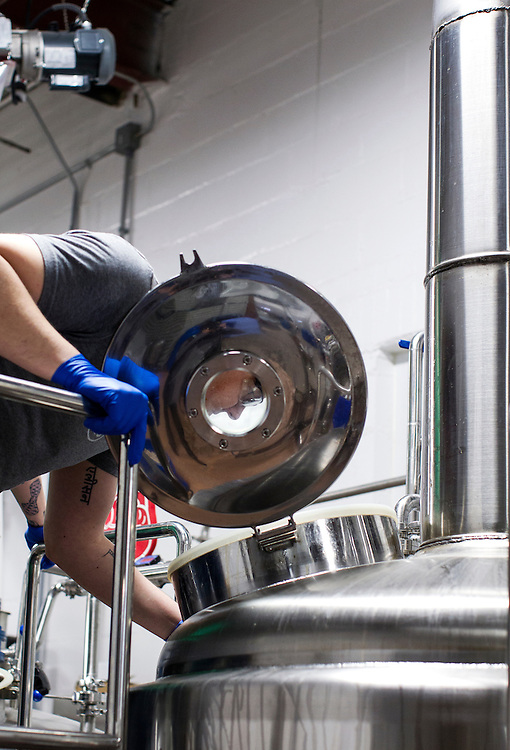 Jason Westplate checks on the progress of Big Watt Cold Beverage Co.'s cold press coffee brewing in tanks at Burning Brothers Brewing in St. Paul December 15, 2015. Westplate is one of 5 founders of sister companies Five Watt Coffee and Big Watt Cold Beverage Co.