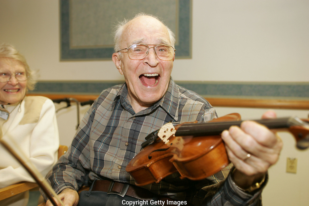LACEY, WA - MARCH 4: Howard Scott laughs while trying out the handmade violin from his grandson, Nolle Pritchard during his 87th birthday party at the assisted living home where he resides in Lacey, Wa. Scott began making the violin 50 years ago while serving time as a conscientious objector in a federal prison and never finished it. His grandson, Nolle Pritchard, got a classmate, Jess Fox, to finish making it at the North Bennet Street School. (Photo by John Froschauer/Getty Images for the Boston Globe)