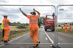 HS2 workers observe an anti-HS2 activist who had occupied a trailer transporting wood chip in order to try to prevent or delay tree felling alongside the Fosse Way in connection with the HS2 high-speed rail link on 24th August 2020 in Offchurch, United Kingdom. The controversial HS2 infrastructure project is currently expected to cost £106bn and will destroy or significantly impact many irreplaceable natural habitats, including 108 ancient woodlands.