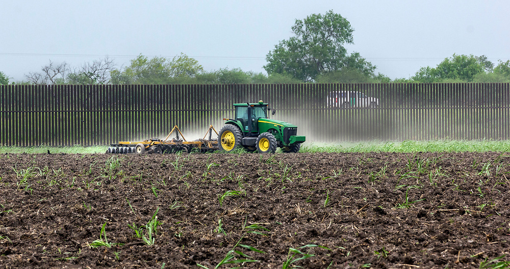 A Customs and Border Protection Agent vehicle patrols the border wall near Brownsville, Texas, whilst a farmer ploughs his field.