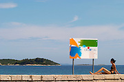 A young woman in bikini looking away on a wall, a sign saying Welcome to Croatia, on the beach by the blue sea, and island in the background Orebic town, holiday resort on the south coast of the Peljesac peninsula. Orebic town. Peljesac peninsula. Dalmatian Coast, Croatia, Europe.