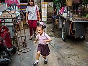"""26 FEBRUARY 2019 - BANGKOK, THAILAND: A girl in her school uniform runs ahead of her mother in Bangkok's Chinatown district. Bangkok has one of the largest """"Chinatown"""" districts in the world. About 14% of all Thais have some Chinese ancestry and Chinese cultural practices are incorporated in many facets of Thai daily life.       PHOTO BY JACK KURTZ"""