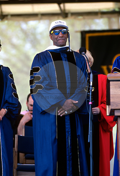 Comedian and actor Bill Cosby stands in cap and gown as he receives an honorary degree after giving the commencement address during graduation ceremonies at the George Washington University May 18, 1997 in Washington, DC.