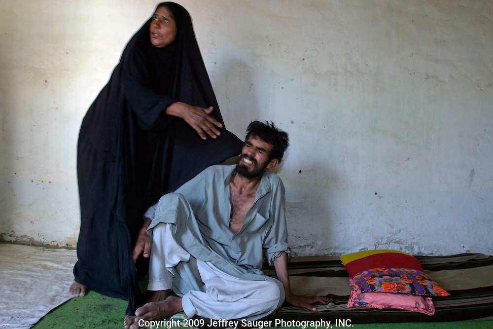 """Aoum Hussein tries to explain what happened to her brother Aowth Abde Nassr in their home in the modernized center of the village Suq ash Shuyukh on the outskirts of Nasiriyah, Iraq, Sunday, August 3, 2003. ..Nassr was forced into the Iraqi armed services and went AWOL as many did during the 1980's and 90's. When he was caught, he was beaten so badly that he is now brain damaged, cannot speak, and suffers severe convulsions. His sister says he went mad after they beat him...Emad Al-Kasid was visiting the neighborhood he grew up in for the first time since his family fled in 1991. He met the woman while visiting his elementary school. (As we left, he handed her a stack of Iraqi Dinar hidden in a piece of paper. He said he had no idea how much he gave her. I think it had to be between 10,000 to 15,000 by counting out a comparable sized stack.)..He took an indefinate amount of time from his satellite and Arab media company in Dearborn, MI, to come home with his family. On his own, and with his own money he's been meeting with Iraqi businessmen, religious leaders and politicians trying to find ways to bring business and democracy to Iraq. ..""""Can you imagine being away from you home and family for 13 years?"""" he asks. """"I'm torn, do come here to stay and leave all I've built in the U.S.?""""..He is hoping to teach members of his tribe, Al Hacham Al-kasid, and village that there is help available; they just have to ask for it. Another goal of this trip is to see for himself whether Iraq is safe enough for exiles to return and for foreign investment to come in...Since the 1991 uprising against Saddam Hussein in Shiite dominated Southern Iraq, people of this area have suffered greatly through his methods of disrupting daily life. For example, modernization came to a hault as money was diverted to Baath Party strongholds. Check points on on every other corner made it nearly impossible to go to work, the doctor, or visit family. Teachers made $5 U.S. per month and had to spend alm"""