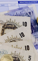 File photo dated 15/04/14 of notes and coins on a payslip, as a new report has found that employers have awarded median pay rises of 2\% this year, with forecasts that the figure will not increase in 2018.