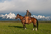 A wrangler taking time to look over his shoulder as his horse rests in front of the Grand Teton mountain range in historic Jackson Hole, WY