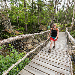 "A woman crosses Haley Brook  on ""Wounded Warrior Bridge"" near Saddleback Lake in Dallas Plantation, Maine. High Peaks region, near Rangeley."