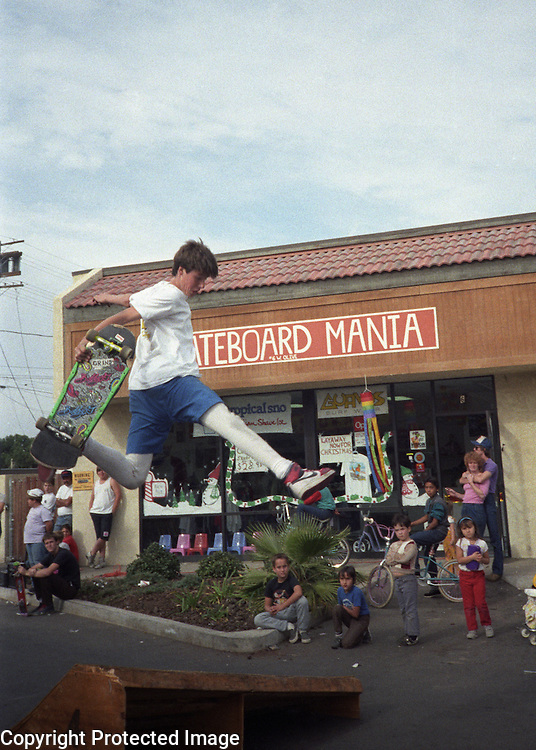 Tom Knox catches air from a jump ramp during a skateboarding demonstration at Skateboard Mania skateboard shop during 1986 in Porterville, California.