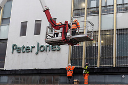© Licensed to London News Pictures. 29/10/2020. LONDON, UK.  Workmen install Christmas lights to the exterior of Peter Jones department store in Sloane Square.  The store is part of the John Lewis group whose flagship store in Oxford Street has been granted permission to turn half of the building into offices as the company undergoes a restructuring plan to stem a downturn in business performance suffered during the ongoing coronavirus pandemic. In addition, staff will not be paid their annual bonus for the first time since 1953.  Photo credit: Stephen Chung/LNP