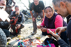 Tibetan Buddhist woman selling her wares on the side of the road during Motorcycle Sherpa's Ride to the Heavens motorcycle adventure in the Himalayas of Nepal. On the third day of riding, we went from Pokhara to Kalopani. Wednesday, November 6, 2019. Photography ©2019 Michael Lichter.