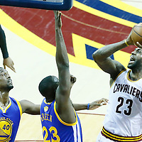08 June 2016: Cleveland Cavaliers forward LeBron James (23) goes to the basket against Golden State Warriors forward Draymond Green (23) and Golden State Warriors forward Harrison Barnes (40) during the Cleveland Cavaliers 120-90 victory over the Golden State Warriors, during Game Three of the 2016 NBA Finals at the Quicken Loans Arena, Cleveland, Ohio, USA.