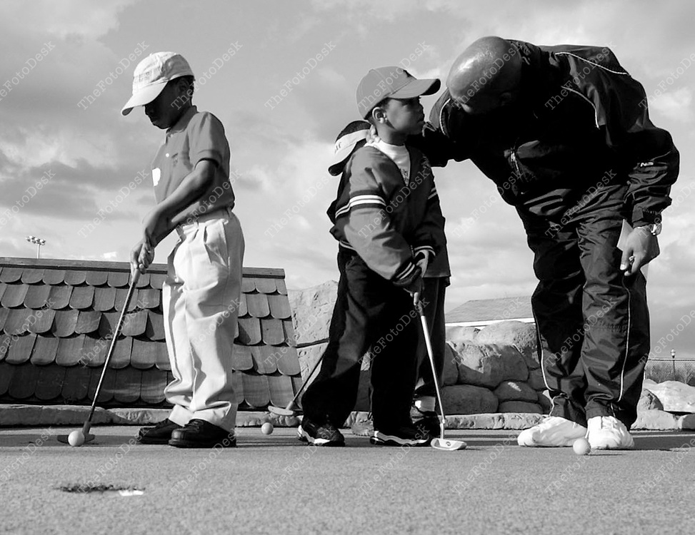 An African American male with boys golfing  (Brian Branch Price)