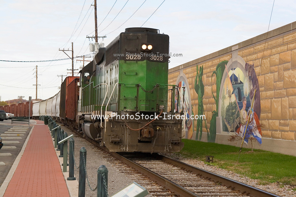 """Cape Girardeau, Missouri MO USA, A train running along the flood-wall with a series of wall paintings on it called """"Mississippi river tales"""" at Cape Girardeau, MO."""