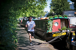© Licensed to London News Pictures. 23/06/2020. London, UK. A man jogging along the towpath of Grand Union Canal at Little Venice in central London at the beginning of a warm summers day. Record temperatures are expected this week as the UK starts to relax lockdown restrictions, introduced earlier this year to prevent the spread of COVID-19. Photo credit: Ben Cawthra/LNP
