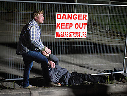 © Licensed to London News Pictures . FILE PICTURE DATED 14/09/2013 . Bury , UK . A man who appears the worse for where stumbles to the ground by railings at the exit and another man attempts to pull him up , as the two laugh . The Ramsbottom Festival . Photo credit : Joel Goodman/LNP
