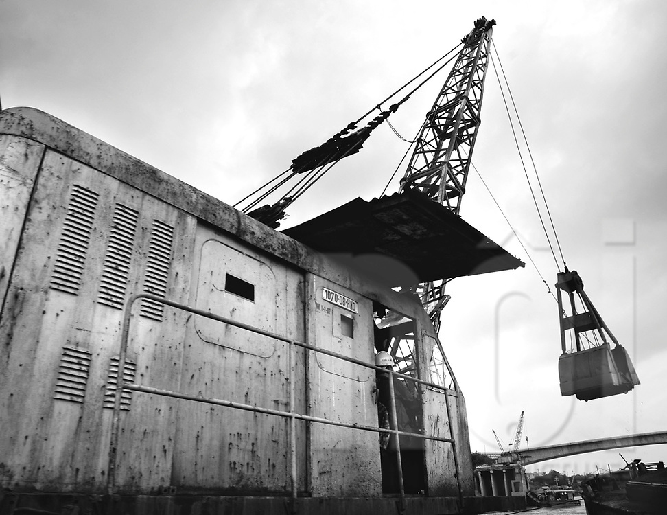 Old rusty crane excavates archoals in a harbour along red river. Hanoi, Vietnam, Asia