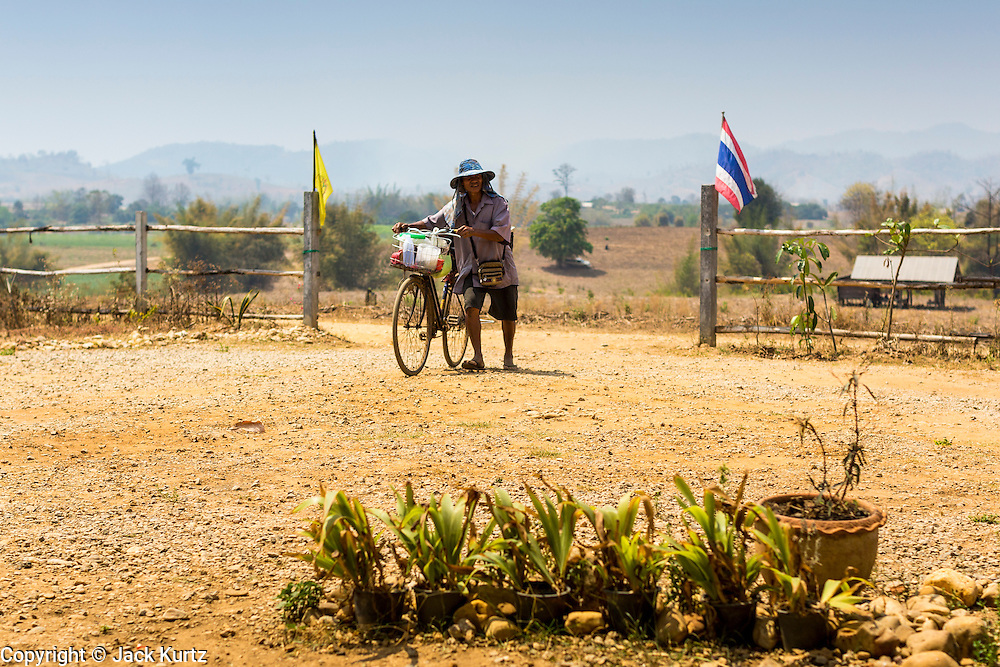 03 MARCH 2104 - MAE KASA, TAK, THAILAND: A Burmese snack vendor pushes his bicycle into the Sanatorium Center for Border Communities in Mae Kasa, about 30 minutes north of Mae Sot, Thailand. He sells traditional Burmese sweets to the patients. The Sanatorium provides treatment and housing for people with tuberculosis in an isolated setting for about 68 patients, all Burmese. The clinic is operated by the Shoklo Malaria Research Unit and works with several other NGOs that assist Burmese people in Thailand. Reforms in Myanmar have alllowed NGOs to operate in Myanmar, as a result many NGOs are shifting resources to operations in Myanmar, leaving Burmese migrants and refugees in Thailand vulnerable. Funding cuts could jeopardize programs at the clinic. TB is a serious health challenge in Burma, which has one of the highest rates of TB in the world. The TB rate in Thailand is ¼ to ⅕ the rate in Burma.        PHOTO BY JACK KURTZ