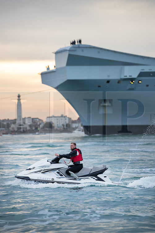© Licensed to London News Pictures. 16/08/2017. Portsmouth, UK. A man on a jet ski passes the Royal Navy's new aircraft carrier HMS  Queen Elizabeth as she enters her home port of Portsmouth for the first time. The new ship at 65,000 tonnes is the biggest warship ever built in the UK. Photo credit: Peter Macdiarmid/LNP
