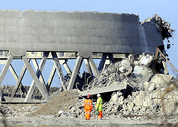 © Licensed to London News Pictures. 11/03/2012. Kent, UK. Builders looks at the remains of one of the cooling towers after the demolition has taken place. Richborough Power Station Towers pictured before the demolition today, 11 March 2012. The former Richborough power station site has not been used since its closure in 1996 .Three cooling towers and a giant chimney which have dominated the east Kent skyline for 50 years will be destroyed. Photo credit : Grant Falvey/LNP