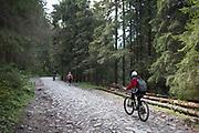 Cyclists climb along a cobbled road in Dolina Chocholowska, a hiking route in the Polish Tatra mountains, on 17th September 2019, near Zakopane, Malopolska, Poland.