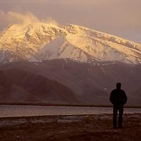 CHINA, Xinjiang. Mark Newcomg (MR) by Lake Karakul. 7546m Mustagh Ata (Pamir Mts.) bkg.