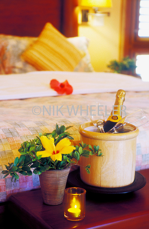 Champagne bucket, flowers, and candle in bedroom of Pink Sands Resort on Harbour Island.