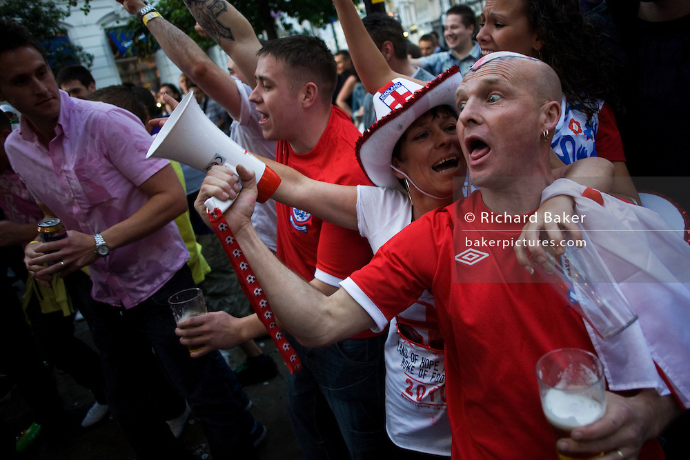 England World Cup football fans watch their team's opening match versus USA on TV outside West End pub.
