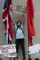 © Licensed to London News Pictures. 03/06/2020. London, UK. A young boy climbs the Cenotaph in Whitehall taking part in a demonstration organised by group Black Lives Matter in Hyde Park for the American George Floyd who died whilst being arrested by US policemen Derek Chauvin. His death has caused civil unrest in some US cities. Photo credit: Ray Tang/LNP