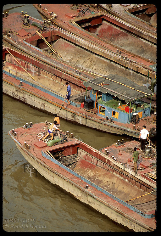 Men tie barges beside one another on Huangpu River in this view from bridge in Shanghai (v). China