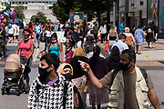 With just five more days to the official freedom day planned for the 19th July, people, many of whom are wearing face masks, come to the city centre retail shopping district on 14th July 2021 in Birmingham, United Kingdom. After months of lockdown, but with case numbers rising, in particular that of the Delta Variant, there is hope that life will start to return to normal, with restrictions like the compulsory wearing of face coverings in public spaces ending.