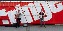 Male buskers perform in front of ticket office of the Edinburgh Fringe festival , Edinburgh , Scotland, UK