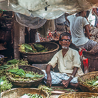 A man vends fruits and vegetbles in a bazaar in Dhaka, Bangladesh.