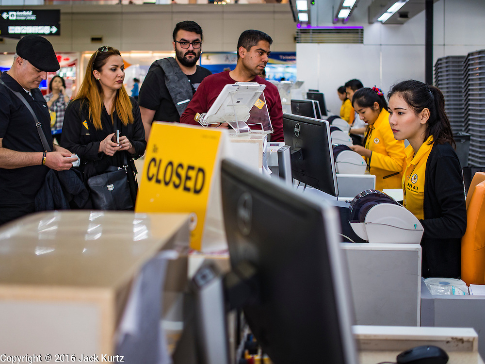 """23 FEBRUARY 2016 - BANGKOK, THAILAND: Passengers check in for domestic flights on Nok Air at Don Mueang Airport in Bangkok. Nok Air, partly owned by Thai Airways International and one of the largest and most successful budget airlines in Thailand, cancelled 20 flights Tuesday because of a shortage of pilots and announced that other flights would be cancelled or suspended through the weekend. The cancellations came after a wildcat strike by several pilots Sunday night cancelled flights and stranded more than a thousand travelers. The pilot shortage at Nok comes at a time when the Thai aviation industry is facing more scrutiny for maintenance and training of air and ground crews, record keeping, and the condition of Suvarnabhumi Airport, which although less than 10 years old is already over capacity, and facing maintenance issues related to runways and taxiways, some of which have developed cracks. The United States' Federal Aviation Administration late last year downgraded Thailand to a """"category 2"""" rating, which means its civil aviation authority is deficient in one or more critical areas or that the country lacks laws and regulations needed to oversee airlines in line with international standards.         PHOTO BY JACK KURTZ"""