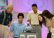 """Participants and antique experts inspect a vase to see whether it is fake or real on the set of """"Collector's World,"""" a Beijing Television game show. Participants bring their antiques to be appraised by experts and if the articles are deemed to be fakes they are smashed with a golden hammer. The show plays on the country's turbulent modern history, and on the widespread fear of being deceived in a country where everything from DVDs to drugs can be faked."""